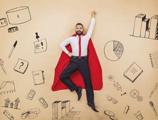 Manager in a cloak of superman. Studio shot on beige background