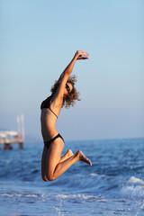 Woman jumping in bikini, on sea water. Relax, vacation