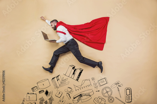 Manager in a cloak of superman. Studio shot on beige background
