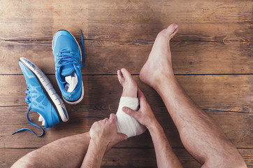Unrecognizable injured runner sitting on wooden floor background