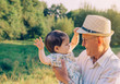 Baby girl playing with hat of senior man outdoors