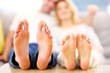 Barefeet of a happy couple lying on a sofa