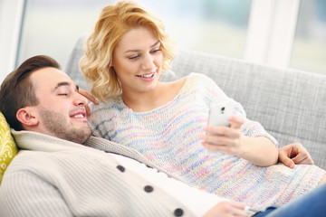Happy couple relaxing at home and using smart phone