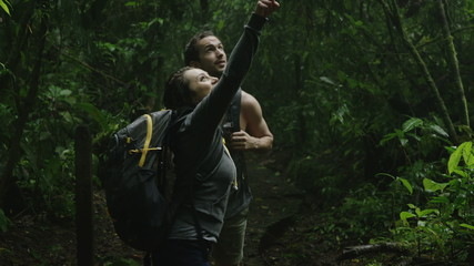 Medium shot of curious couple hiking and exploring jungle / Arenal, Costa Rica