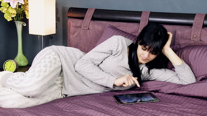 Young woman playing with tablet in pajamas in bed