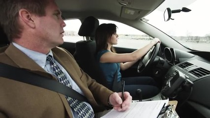 MS Girl (16-17) taking driving test, instructor writing in clipboard / Provo, Utah, USA