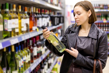 Young woman is choosing wine in the supermarket.