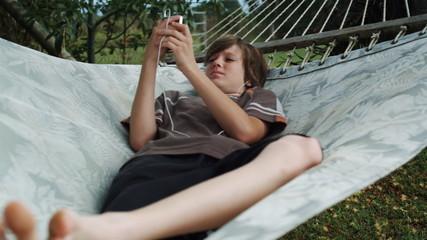 boy in a hammock listening to an iPod