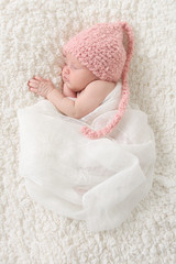 Newborn baby girl wearing a pink hat, wrapped in vintage lace.