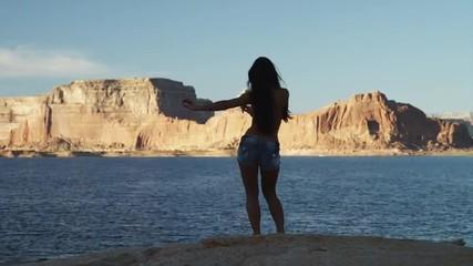 WS DS Rear view of young woman dancing near Lake Powell / Utah, USA