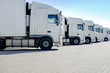 Leinwanddruck Bild - LKW-Spedition, mehrere weiße Laster stehen nebeneinander