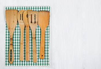 Wooden Cookingware and Cloth Napkin on white wood