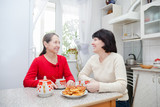 mature women talking in kitchen