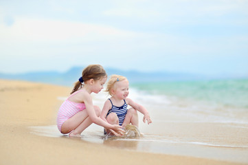 Two little sisters having fun on a beach