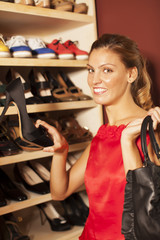 Happy young woman buying shoes
