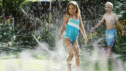 children running in a sprinkler