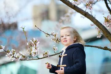 Adorable toddler girl in blooming cherry garden