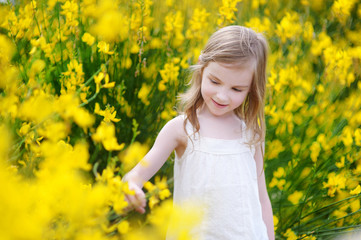 Adorable little girl in blooming flowers