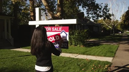 "MS Woman sticking ""Sold"" sign in front of suburban house, Provo, Utah, USA"
