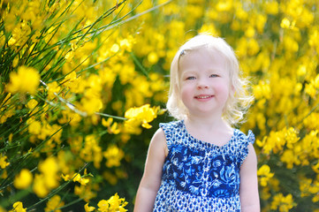 Adorable toddler girl in blooming flowers