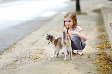 Cute little girl and a cat outdoors