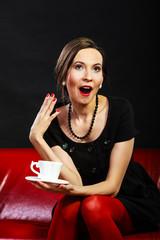 Retro woman holds tea cup sitting on sofa