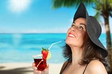 donna sorridente con drink in spiaggia
