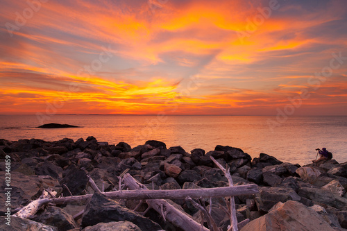 Sunset Photographer on the rocks under orange skies and clouds