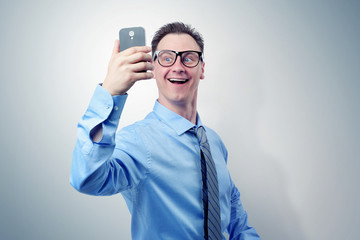 Funny businessman photographing himself on a smartphone