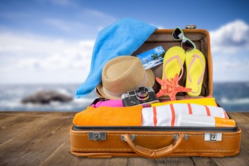 Beach. Top view of an open suitcase with full of summer stuff on