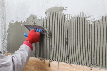 Ceramic Tiles. Tilerman hand spreading adhesive material