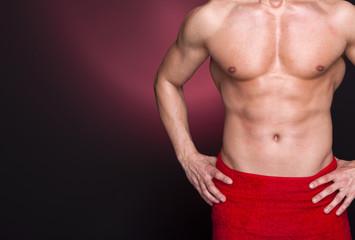 Fit man in red towel against dark background