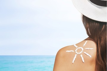 Sun. Woman with suntan lotion on her skin at the beach