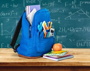 School. Purple backpack with school supplies isolated on white