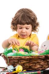 Toddler boy arrange Easter eggs in basket