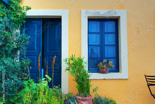 Fotobehang Athene Old house yellow wall with blue door and window. Greece Santorin