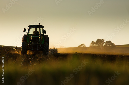 Plakát Tractor in sunset plowing the field