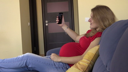 Happy pregnant woman shoot selfie with smartphone, browse photo