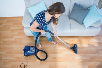 Woman using vacuum cleaner on wooden floor