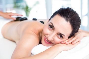 Smiling brunette getting hot stone massage
