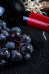 Red wine bottle with grapes and corkscrew