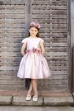 Niña rubia con vestido y tocado rosa apoyada en valla