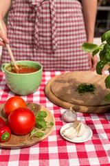 Frau rührt Soße mit mediterranen Zutaten