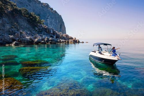 Woman relaxing on boat in sea near rocky shore. Traveling island - 82380076