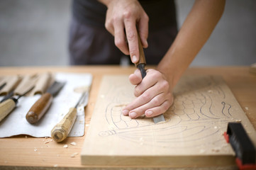 Artist carves a wooden plate with a chisel