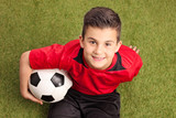 Junior football player sitting on grass and smiling