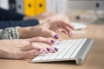 Female fingers typing on keyboard