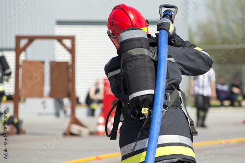 strażak z wężem gaśniczym