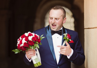 Young handsome bridegroom with a bouquet for his bride