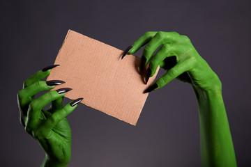Green hands with long black nails holding empty piece of cardboa